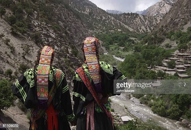 Girls from the polytheistic Kalash tribe look down into their remote mountain village during the Joshi spring festival May 15, 2008 in the Chitrali...