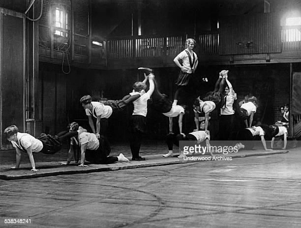 Girls from the Sargent School for Physical Education making a pyramid for their upcoming show at the Boston Arena Cambridge Massachusetts circa 1926