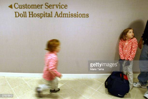 Girls gather near a sign for the 'doll hospital' during a press preview for the opening of American Girl Place New York November 7 2003 in New York...