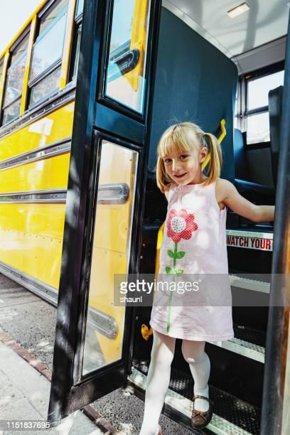 スクールバスを降りる女の子 - 降り立つ ストックフォトと画像
