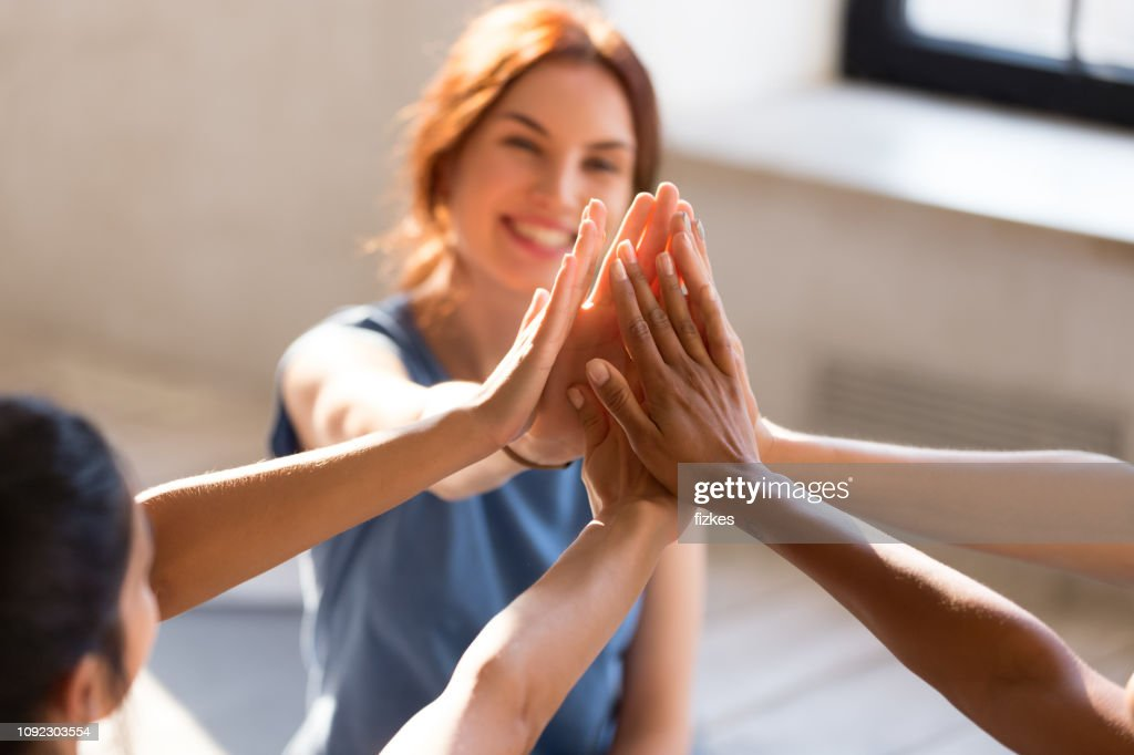 Girls giving high five, close up focus on hands : Stock Photo