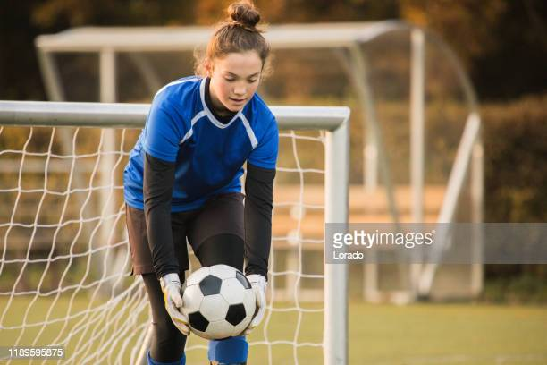 girls goalkeeper playing soccer during a football match - goalkeeper stock pictures, royalty-free photos & images