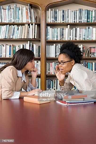 Girls gossiping in library