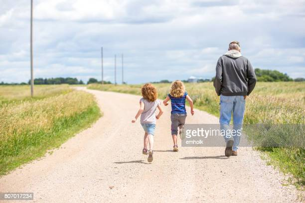 Girls & Grandpa Walking & Running Out Rural Gravel Driveway