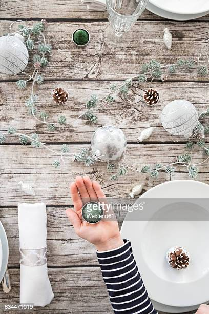 Girls hand holding tea light in front of laid table at Christmas time