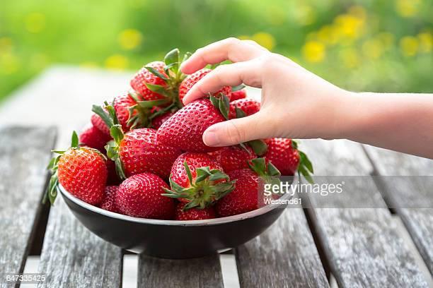 girl's hand taking strawberry - mädchen stock-fotos und bilder