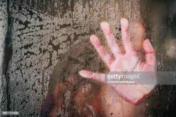 Girls hand wiping steam from the shower glass