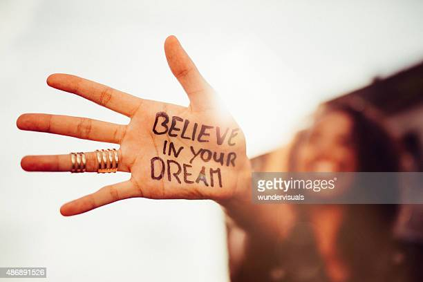 "girl's hand with ""believe in your dreams"" written on it - geloof stockfoto's en -beelden"