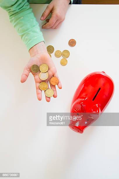 Girls hand with coins and a red piggy bank