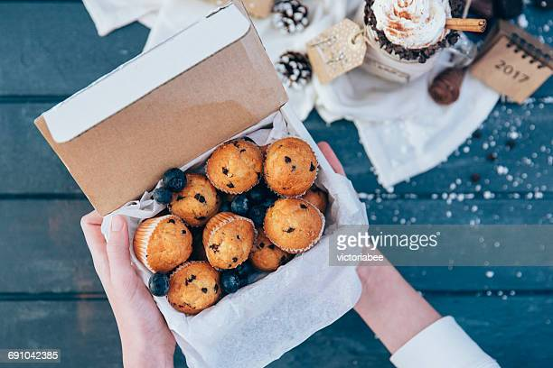 Girl's hands holding box of blueberry muffins