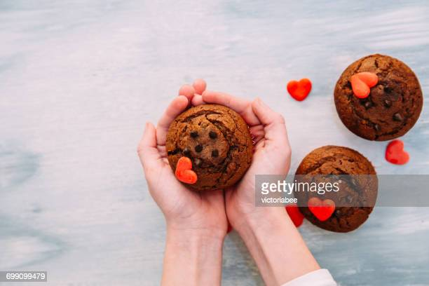 Girl's hands holding chocolate muffins with hearts