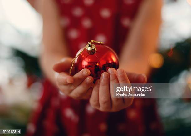 girl's hands holding christmas ornament