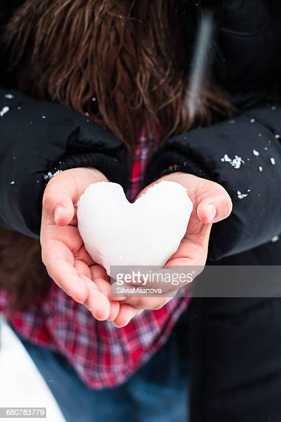 Girl's hands holding heart shaped snow
