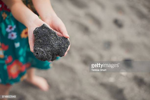 girl's hands holding lava rock in hawaii - volcanic rock stock pictures, royalty-free photos & images