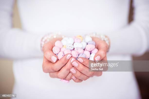 Girl's Hands Holding Pastel Coloured Easter Eggs
