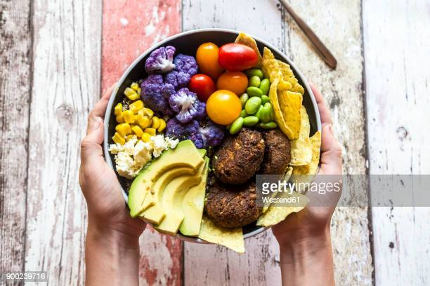 girl's hands holding quinoa veggie bowl of vegetables, feta, nachos and quinoa fritters - vegetarian food stock pictures, royalty-free photos & images