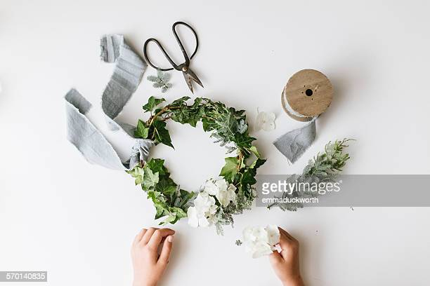 Girl's hands making a festive christmas foliage wreath