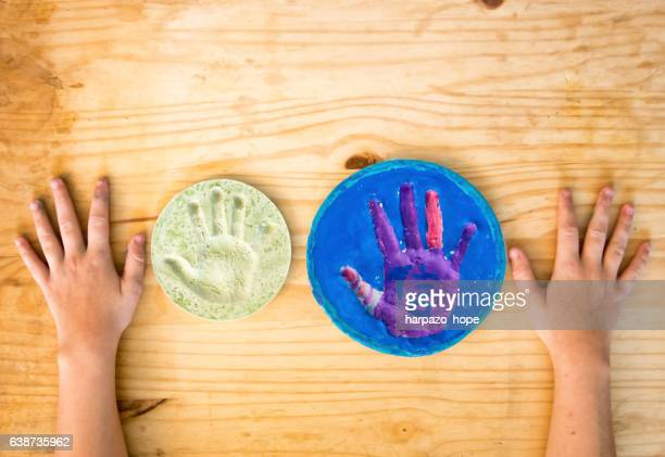 A girl's hands placed beside plaster hand prints.