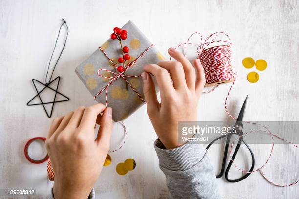 girl's hands wrapping christmas present - avvolto foto e immagini stock