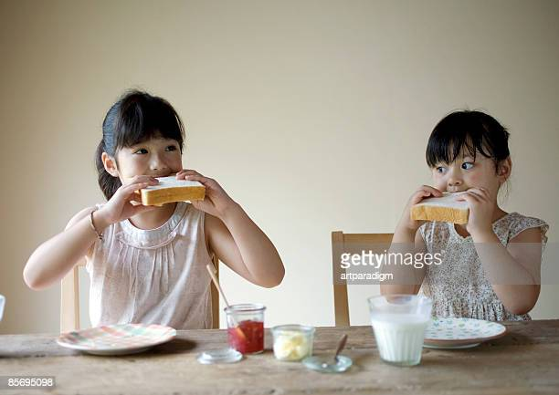 Girls having a big mouthful of bread