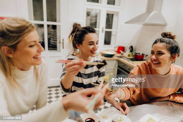 girls having dinner together at home - chopsticks stock pictures, royalty-free photos & images