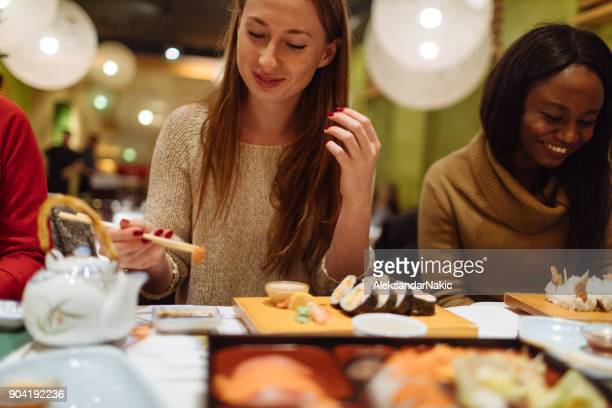 girls having dinner together in chinese restaurant - sushi restaurant stock photos and pictures