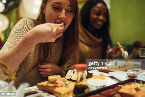 girls having dinner together - sushi restaurant stock photos and pictures