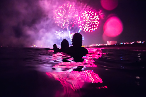 Girls having fun enjoying and contemplating the colorful fireworks at night taking a bath in the beach with colorful reflection. - gettyimageskorea