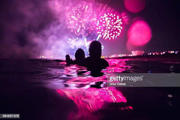 Girls having fun enjoying and contemplating the colorful fireworks at night taking a bath in the beach with colorful reflection.