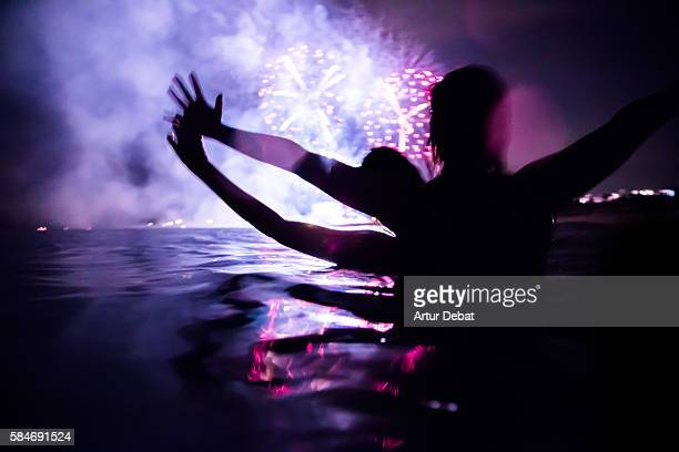 Girls having fun enjoying the colorful fireworks at night taking a bath in the beach with colorful reflection and raising arms.
