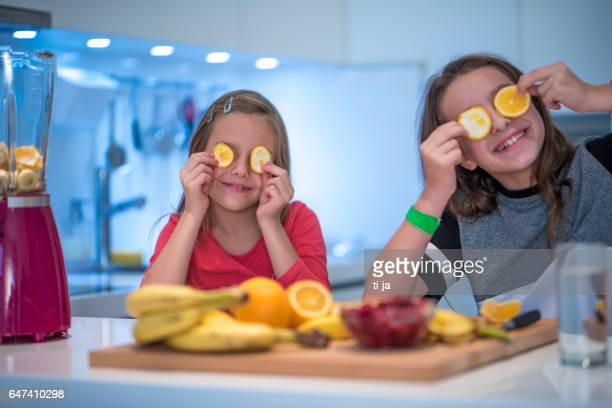 Girls having fun in a kitchen with fruit