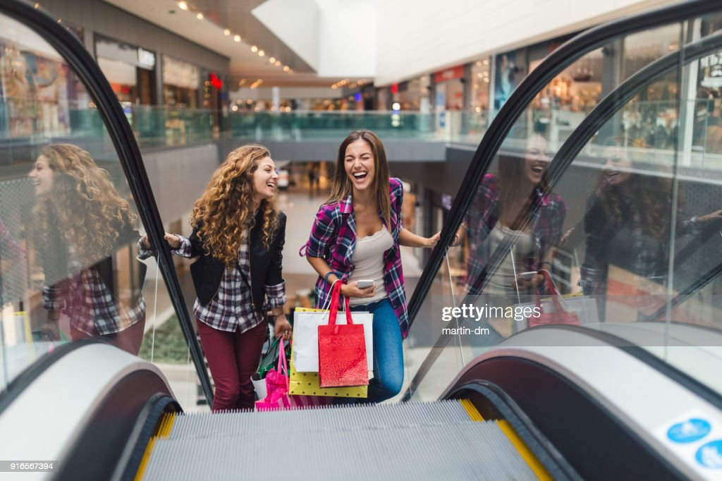 Girls having fun in the shopping center : Stock Photo