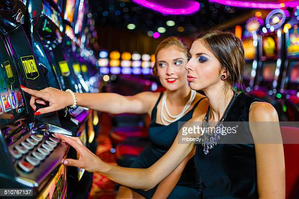 girls having fun with slot machine in casino - teen pokies stock photos and pictures
