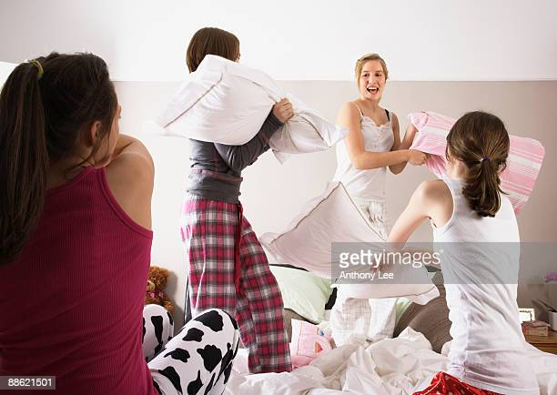 girls having pillow fight at slumber party - girl fight stock photos and pictures