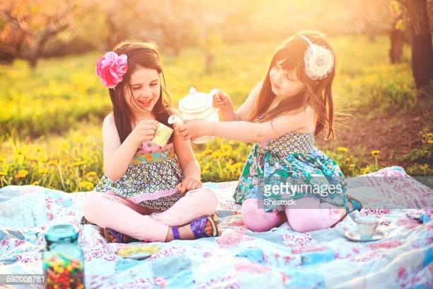 Girls having tea party picnic in rural field