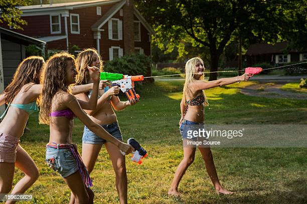 girls having water fight with water pistols - squirt foto e immagini stock