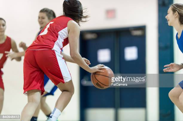 girls high school basketball game - charging sports stock photos and pictures