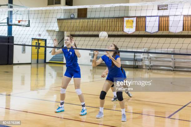 girls high school volleyball game - spiking stock photos and pictures