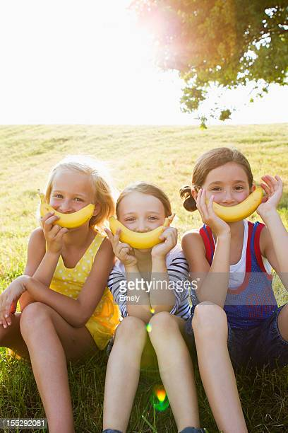 Girls holding bananas over mouths