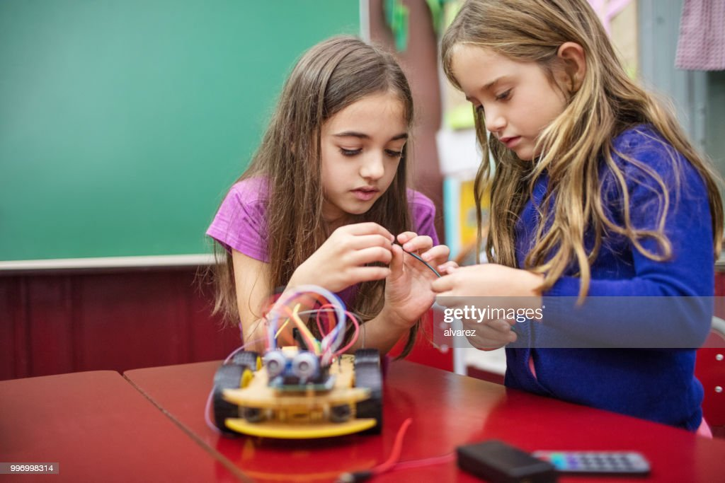 Girls holding cable while making project in class : Stock Photo