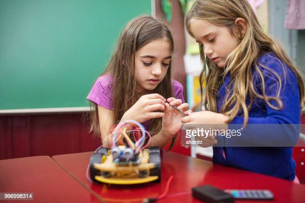 Girls holding cable while making project in class