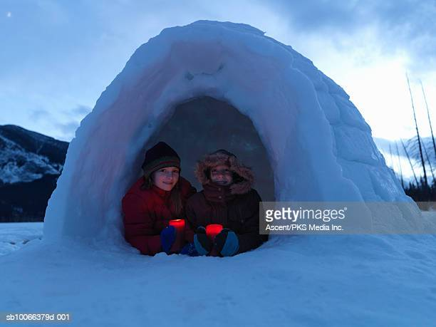 girls (8-13) holding candles in igloo, smiling, portrait - igloo stock pictures, royalty-free photos & images