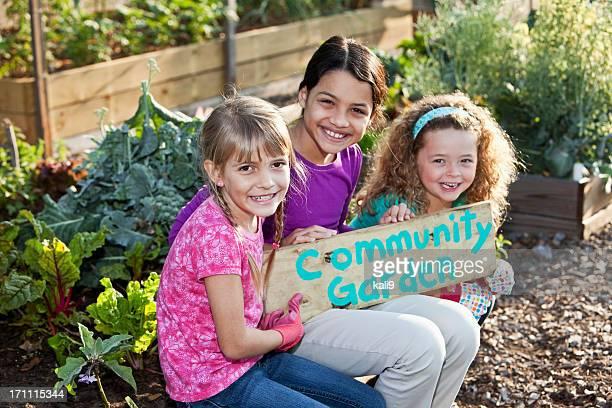 Girls holding community garden sign