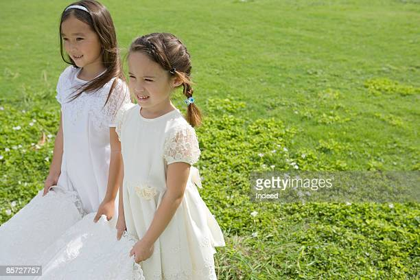 girls holding edge of veil on grass, smiling - bridesmaid stock pictures, royalty-free photos & images