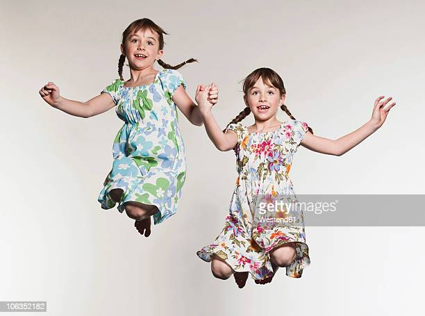 Girls (6-7) holding hands and jumping, smiling