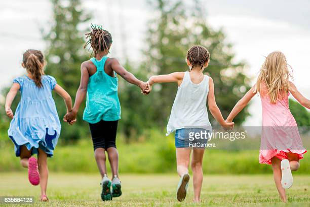 Girls Holding Hands and Running Outside