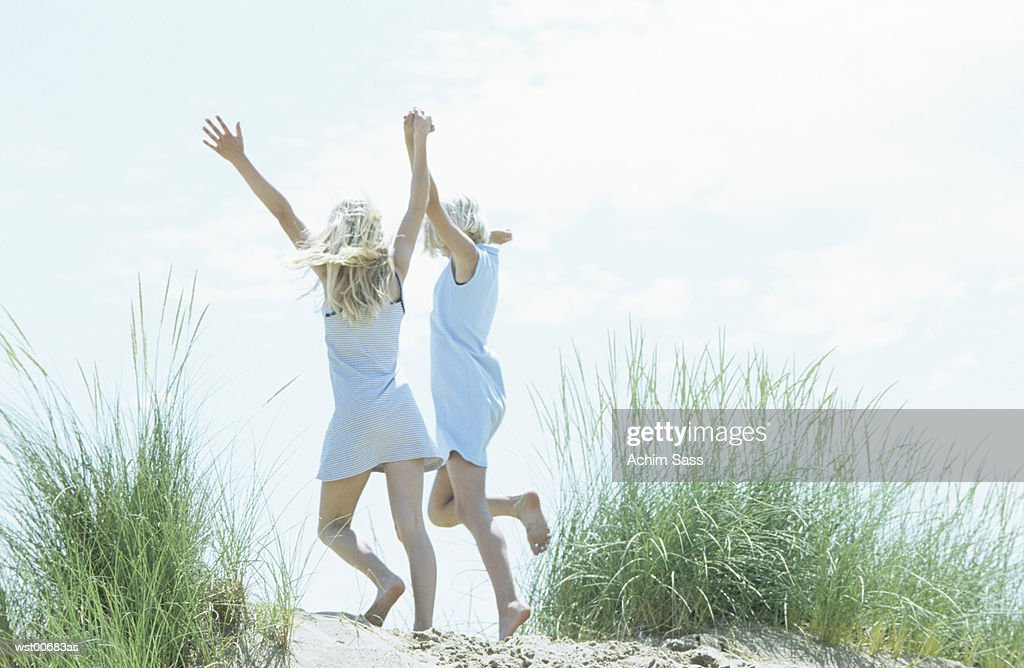 Girls holding hands and skipping : Stockfoto