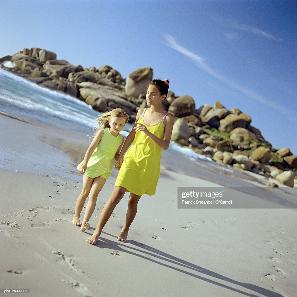 Girls holding hands while walking on beach : Stockfoto