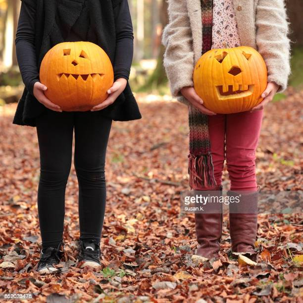 girls holding jack o' lantern in the woods. - naughty halloween stock photos and pictures