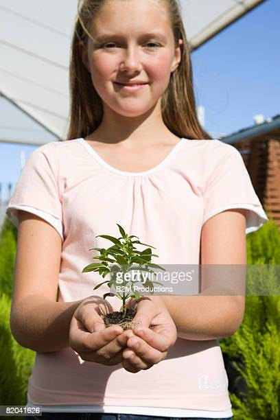 Girls (12-13 years) Holding plant